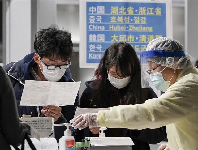 9일 일본 지바현 나리타 국제공항에서 탑승객들이 공항에 도착 후 검역 절차를 거치고 있다. 현지 검역관들이 검역을 하고 있다. 지바=EPA연합뉴스
