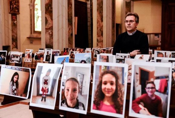 한 이탈리아 신부가 22일 텅 빈 성당을 신자들이 보내 온 사진으로 채우고 있다. 연합뉴스