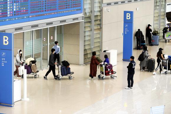 정부가 27일부터 미국발 입국자에 대한 검역을 강화하기로 했다. 25일 인천국제공항 제2터미널 입국장에서 방역당국 관계자가 유럽발 항공기 승객들을 살피고 있다. 연합뉴스