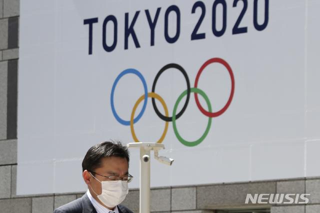 [도쿄=AP/뉴시스]지난 25일(현지시간) 일본 도쿄도청에 걸린 2020 도쿄올림픽 로고 앞을 한 행인이 마스크를 쓰고 걸어가고 있다. 오는 7월 예정돼 있던 도쿄올림픽은 신종 코로나바이러스 감염증(코로나19) 여파로 내년으로 연기됐다. 2020.3.25.