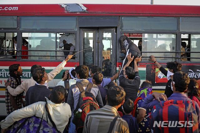 [뉴델리=AP/뉴시스] 지난달 28일 인도 뉴델리의 공영버스정류장에 버스가 들어서자 사람들이 앞다퉈 몰려가고 있다. 신종 코로나바이러스 감염증(코로나19) 확산을 막기 위해 13억 명의 외출을 금지한 인도에서는 도시 빈민 60만명이 대이동을 시작했다. 2020.4.1.