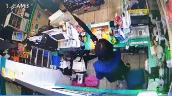 편의점에서 근무 중이던 김모(50·여)씨가 A씨가 편의점에 들어온 것을 확인하고 놀라 우산을 든 모습. 편의점 CCTV영상 캡쳐