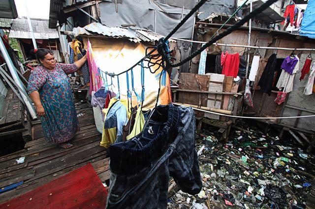 자카르타 도심 내 빈민촌 풍경. 집 아래 강은 쓰레기로 가득하다. 안타라통신 캡처