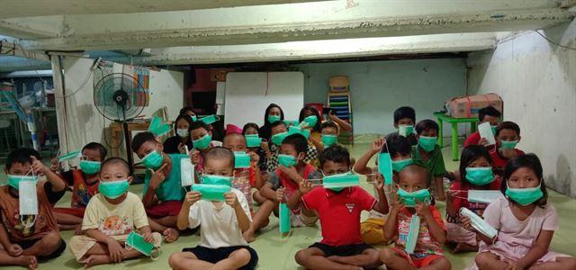인도네시아 빈민촌 아이들이 재인도네시아한인회로부터 마스크를 받고 직접 써보고 있다. 재인도네시아한인회 제공