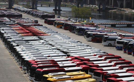 4일 오전 서울 송파구 탄천주차장이 주말임에도 불구하고 영업을 나가지 못한 관광버스들로 가득 차 있다. 〈br〉  정부는 이날 '강화된 사회적 거리두기'를 19일까지 2주간 연장한다고 밝혔다. 연합뉴스