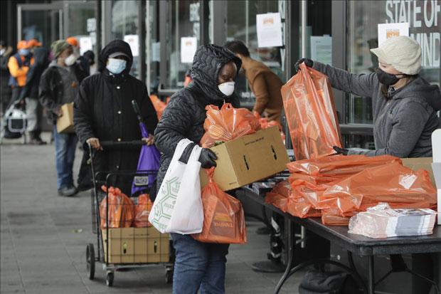지난달 24일(현지시간) 미국 뉴욕 브루클린의 한 푸드 뱅크에서 자원봉사자들이 주민들에게 식량키트를 건네고 있다./사진=AP 연합뉴스