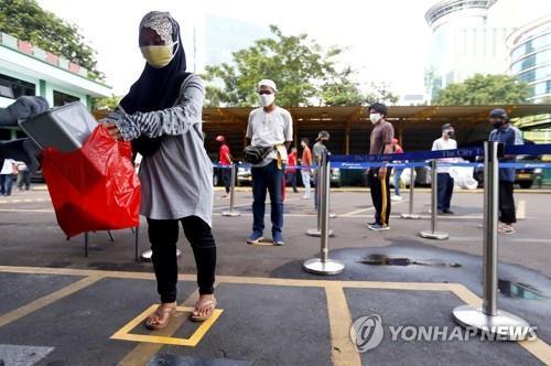 자카르타 '쌀 ATM기'에서 쌀 1.5㎏ 배급받는 여성 [로이터=연합뉴스]