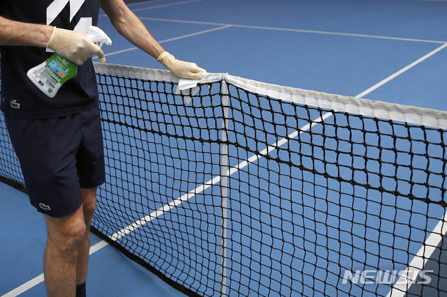 [파리=AP/뉴시스]니콜라 마위(프랑스)가 13일(현지시간) 프랑스 파리의 프랑스오픈 경기장 인근 프랑스 테니스 연맹 센터에서 팀 의료진과 코트 트레이너들이 지켜보는 가운데 훈련하면서 그물을 소독하고 있다. 2020.05.14.