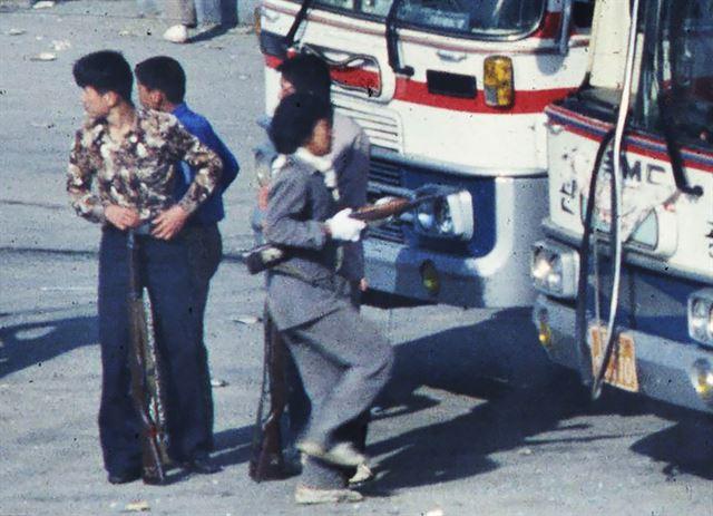 1980년 5월 22일 아침 광주시 외곽 송정리역 광장에서 젊은 남성들 위주의 시위대가 도청으로 출발하기 위해 버스와 트럭에 오르는 가운데 직장 유니폼을 입은 여성이 소총을 들고 버스로 향하고 있다. 박태홍 전 한국일보 기자