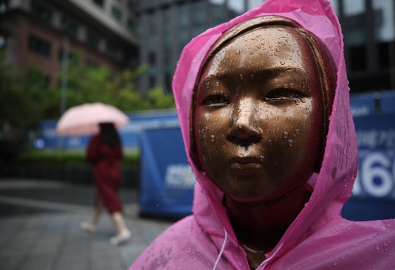 비가 내린 19일 오전 서울 종로구 옛 일본대사관 앞에 설치된 평화의 소녀상에 우비가 씌워져 있다. 연합뉴스