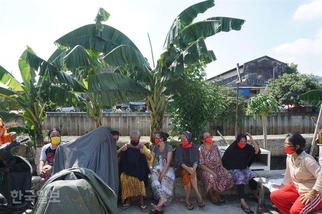 자카르타 북부의 한 빈민촌 주민들이 20일 한국이 선물한 마스크를 끼고 개천가에 앉아 얘기를 나누고 있다. 자카르타=고찬유 특파원