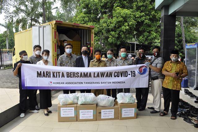 채만용(왼쪽 다섯 번째) 회장 등 인도네시아 땅그랑반튼한인회 회원들이 19일 탕에랑 지역에 코로나19 구호품을 전달하고 있다. 땅그랑반튼한인회 제공