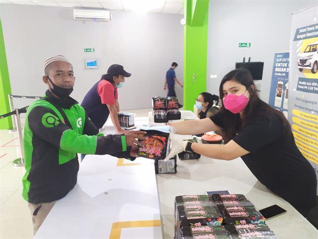 인도네시아 불닭볶음면 유통업체인 헤온즈가 인도네시아 오토바이택시 기사들에게 불닭볶음면을 선물하고 있다. 헤온즈 제공