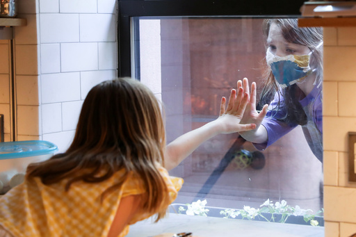 17일(현지시간) 미국 뉴욕 브루클린에서 신종 코로나바이러스 감염증(코로나19) 여파로 한 소녀가 부엌 창문을 사이에 두고 친구와 인사하고 있다. 뉴욕 로이터=연합뉴스