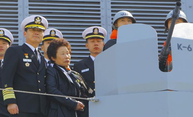 윤청자 여사가 2011년 3월 25일 경기 평택시 해군 제2 함대사령부에서 열린 '3·26 기관총' 기증식에 참석해 K-6 기관총을 살펴보고 있다. 윤 여사 왼쪽은 김성찬 당시 해군참모총장. [원대연 동아일보 기자]