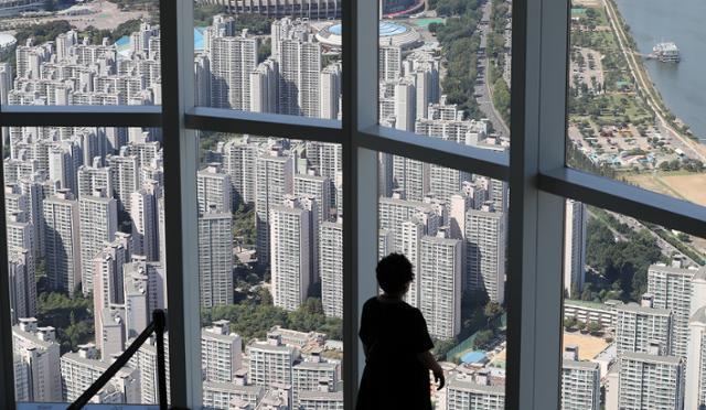 지난 16일 서울 송파구 롯데월드 서울스카이 전망대를 찾은 한 시민이 아파트단지를 내려다보고 있다. 뉴스1